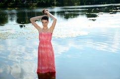 Jeune femme dans la robe rouge dans le lac Images libres de droits