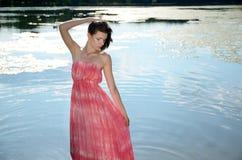 Jeune femme dans la robe rouge dans le lac Photos stock