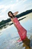 Jeune femme dans la robe rouge dans le lac Photographie stock libre de droits