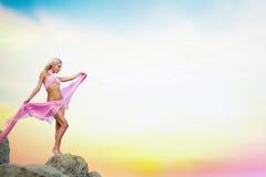 Jeune femme dans la robe se tenant sur une roche photo libre de droits