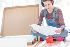 Jeune femme dans la salopette lisant des instructions Photographie stock libre de droits