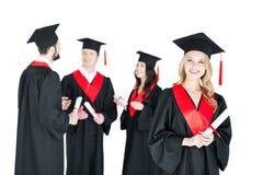 Jeune femme dans la taloche jugeant le diplôme et les amis se tenant derrière Images libres de droits