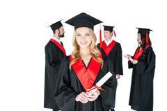 Jeune femme dans la taloche jugeant le diplôme et les amis se tenant derrière Photographie stock libre de droits