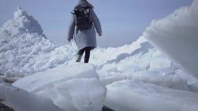Jeune femme dans la veste chaude marchant sur le glacier Nature stupéfiante d'un Pôle du nord ou du sud neigeux Le polaire femell banque de vidéos
