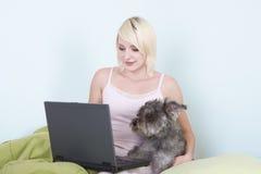 Jeune femme dans le bâti avec le crabot d'ordinateur portatif et de schnauzer Photo stock