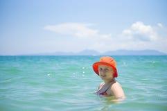 Jeune femme dans le bain orange de chapeau dans l'océan tropical Photographie stock libre de droits