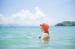 Jeune femme dans le bain orange de chapeau dans l'océan tropical Photos stock