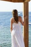 Jeune femme dans le bateau de observation de robe blanche sur la mer Photos libres de droits