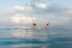Jeune femme dans le bikini lumineux surfant sur un conseil dans l'océan Image stock