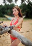 Jeune femme dans le bikini rouge, louchant dans la lumière lumineuse, vent dedans il Photos stock