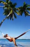 Jeune femme dans le bikini se reposant dans un hamac Photos libres de droits