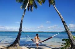 Jeune femme dans le bikini se reposant dans un hamac Photographie stock libre de droits