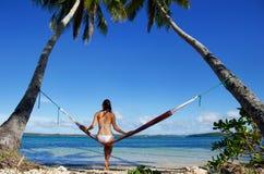 Jeune femme dans le bikini se reposant dans un hamac entre les palmiers, O Image libre de droits
