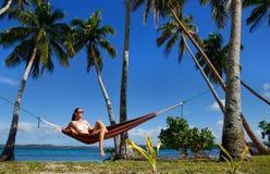 Jeune femme dans le bikini se reposant dans un hamac entre les palmiers, O Images libres de droits