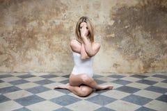 Jeune femme dans le blanc dans la pose de yoga Photo stock