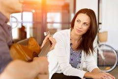 Jeune femme dans le bureau avec l'ami jouant la guitare Photo libre de droits