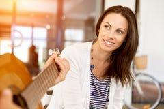 Jeune femme dans le bureau avec l'ami jouant la guitare Image libre de droits