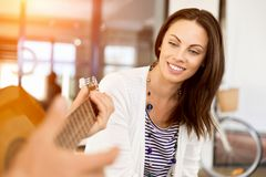 Jeune femme dans le bureau avec l'ami jouant la guitare Photos libres de droits