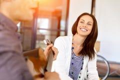 Jeune femme dans le bureau avec l'ami jouant la guitare Images libres de droits