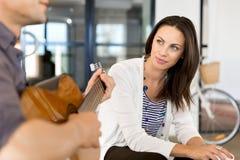 Jeune femme dans le bureau avec l'ami jouant la guitare Photo stock