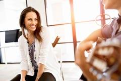 Jeune femme dans le bureau avec l'ami jouant la guitare Image stock