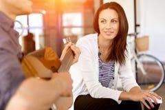 Jeune femme dans le bureau avec l'ami jouant la guitare Images stock
