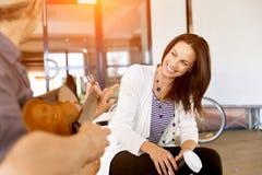 Jeune femme dans le bureau avec l'ami jouant la guitare Photographie stock