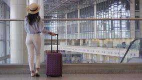 Jeune femme dans le chapeau avec des bagages dans l'aéroport international marchant avec son bagage Passager de ligne aérienne da banque de vidéos