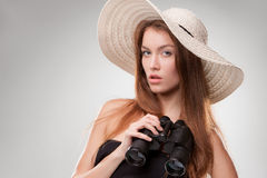 Jeune femme dans le chapeau avec des jumelles Photographie stock libre de droits