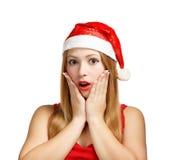 Jeune femme dans le chapeau de Santa étonnée Images stock
