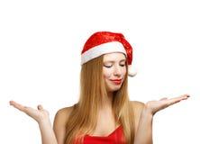 Jeune femme dans le chapeau de Santa avec les mains ouvertes Photo stock