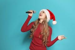 Jeune femme dans le chapeau de Santa chantant dans le microphone photo stock