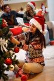 Jeune femme dans le chapeau de Santa décorant un arbre de Noël Images libres de droits