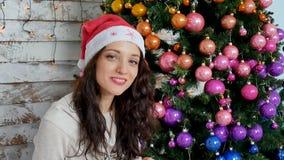 Jeune femme dans le chapeau de Santa près de l'arbre de Noël banque de vidéos