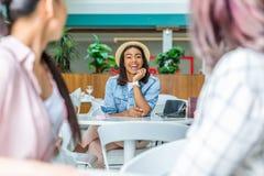 Jeune femme dans le chapeau regardant des amis s'asseyant dans le centre commercial Image libre de droits