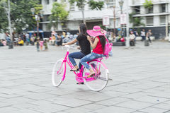 Jeune femme dans le chapeau rose montant une bicyclette dans la ville Personnes actives outdoors Images stock