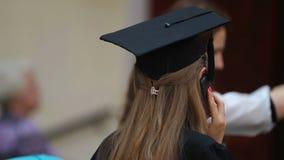 Jeune femme dans le chapeau scolaire parlant au-dessus du téléphone, félicitations sur l'obtention du diplôme banque de vidéos