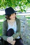 Jeune femme dans le chapeau se reposant à la frontière en pierre Photo libre de droits