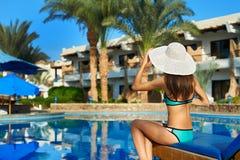 Jeune femme dans le chapeau se reposant sur un canapé du soleil près de la piscine, temps de concept de voyager Détendez pendant  photographie stock libre de droits