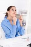 Jeune femme dans le chemisier bleu se reposant au bureau et à rêver Images libres de droits