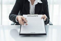 Jeune femme dans le costume dans son bureau montrant une police d'assurances Images libres de droits