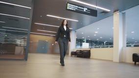 Jeune femme dans le costume descendant le couloir d'un immeuble de bureaux banque de vidéos