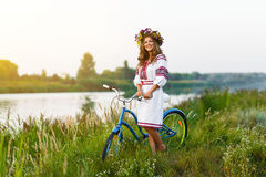 Jeune femme dans le costume folklorique ukrainien national avec la bicyclette Image stock