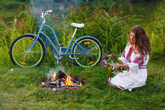 Jeune femme dans le costume folklorique ukrainien national avec la bicyclette Photos stock