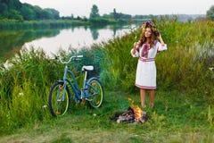 Jeune femme dans le costume folklorique ukrainien national avec la bicyclette Images stock