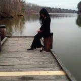 Jeune femme dans le costume noir au lac Image libre de droits