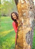 Jeune femme dans le coup d'oeil rose de robe, regardant par derrière l'arbre photo stock