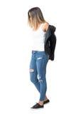 Jeune femme dans le dessus de réservoir et des jeans déchirés enlevant la veste en cuir Images libres de droits