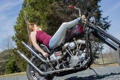 Jeune femme dans le dessus de réservoir s'étendant sur la moto Images libres de droits