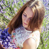 Jeune femme dans le domaine floral de la lavande Photographie stock libre de droits